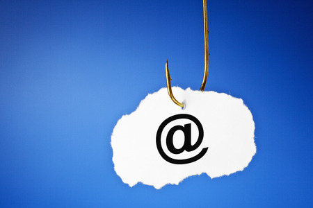 E-mail symbol printed on a piece of paper hooked on a fishing hook. Phishing and data protection concept. Stock Photo - 30661227