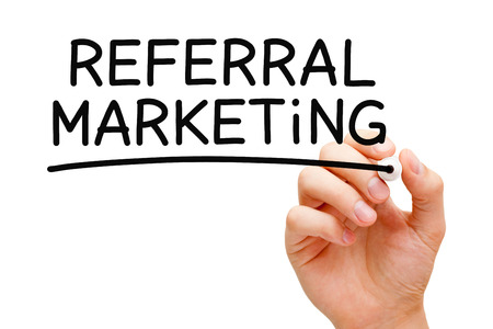 spread the word: Hand writing Referral Marketing with black marker on transparent wipe board.