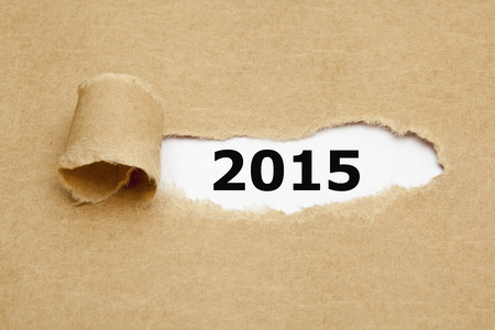 appearing: Year 2015 appearing behind torn brown paper. Stock Photo