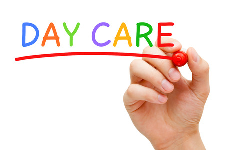day care: Hand writing Day Care with marker on transparent wipe board isolated on white background. Stock Photo