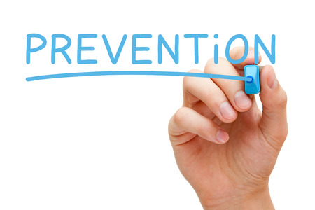 Hand writing Prevention with blue marker on transparent wipe board isolated on white background.
