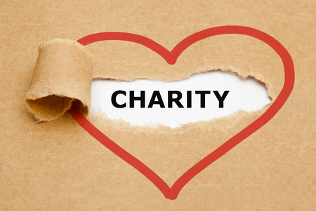 Caridad aparece detrás rasgado de papel marrón. Foto de archivo