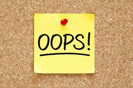 darn: Oops! on yellow sticky note pinned with red push pin on cork board. Stock Photo