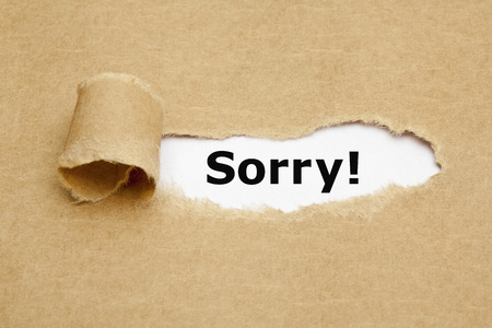 forgiven: The word Sorry appearing behind torn brown paper.