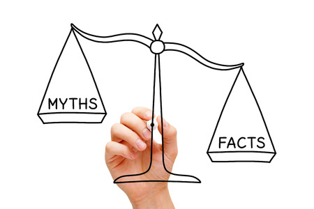 Hand drawing Facts Myths scale concept with black marker on transparent wipe board isolated on white.