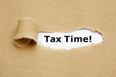 L'expression Tax Time apparaissant derrière papier brun déchiré.