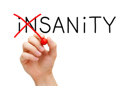 lucidity: Hand turning the word Insanity into Sanity with red marker isolated on white.