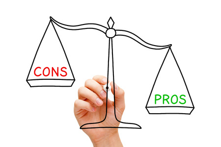 Hand drawing Pros and Cons scale concept with marker on transparent wipe board isolated on white.