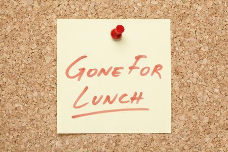 a bulletin board: Gone For Lunch handwritten on a sticky note pinned on a bulletin board.