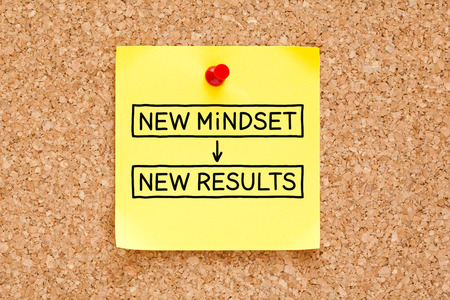 a bulletin board: New Mindset New Results written on a yellow sticky note pinned on a bulletin board.