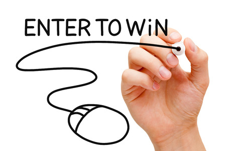 Hand drawing Enter to Win concept with black marker on transparent wipe board.