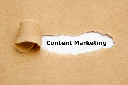 The text Content Marketing appearing behind torn brown paper.
