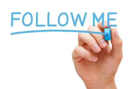Hand writing Follow Me with blue marker on transparent wipe board.
