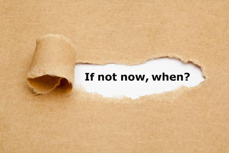 If Not Now When, appearing behind torn brown paper. photo