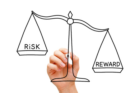 Hand drawing Risk Reward scale concept with black marker on transparent wipe board isolated on white.