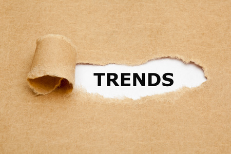 appearing: The word Trends appearing behind torn brown paper. Stock Photo