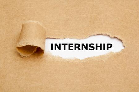 internship: The word Internship appearing behind torn brown paper.