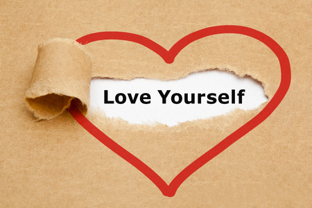self confident: The text Love Yourself appearing behind torn brown paper.