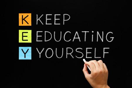 교육: 손 쓰기는 흰색 분필로 칠판에 자신을 교육하십시오. 스톡 콘텐츠