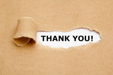 agradecimiento: El texto le agradece que aparece detrás de papel marrón rasgado. Foto de archivo