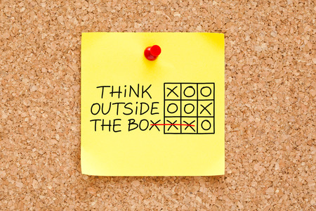 Think Outside The Box tic-tac-toe game concept on yellow sticky note.
