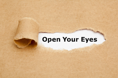 heed: The text Open Your Eyes appearing behind torn brown paper.