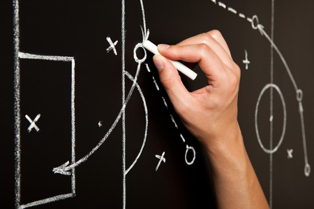soccer sport: Hand drawing a soccer game tactics with white chalk on blackboard. Stock Photo