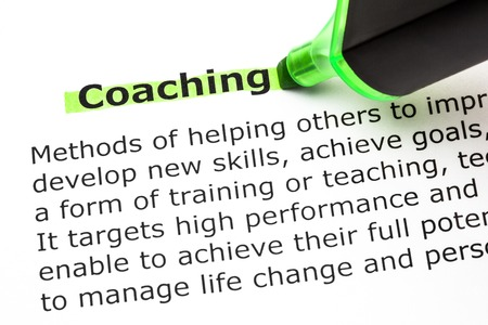 Definition of the word Coaching, highlighted with green text marker. Фото со стока