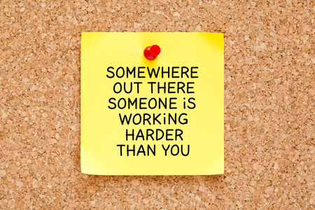 someone: The motivational quote Somewhere Out There Someone is Working Harder Than You handwritten on yellow sticky note.