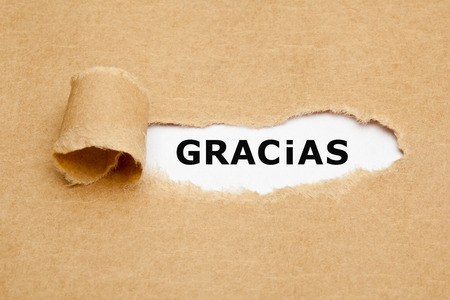 respond: The spanish word Gracias appearing behind torn brown paper.