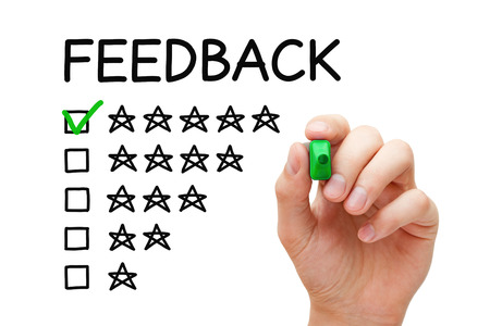 Hand putting check mark with green marker on five stars in feedback form.