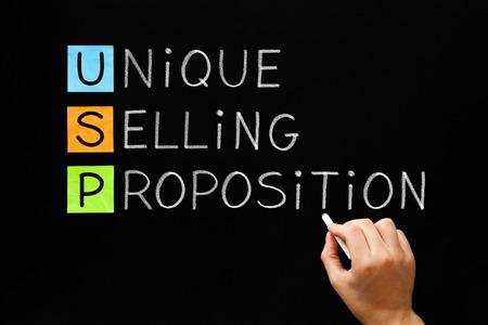 Hand schrijven USP Unique Selling Proposition met wit krijt op een schoolbord.