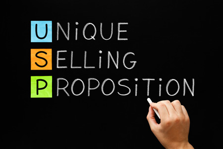 Hand writing USP Unique Selling Proposition with white chalk on a blackboard.