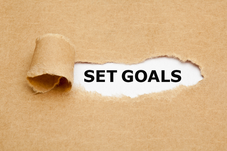 accomplishing: The text Set Goals appearing behind torn brown paper. Stock Photo