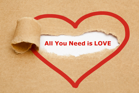 paper heart: The text All You Need is Love appearing behind torn brown paper. Stock Photo