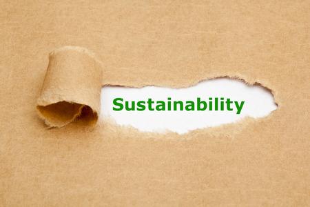Het woord Sustainability comparanten achter gescheurd bruin papier. Stockfoto