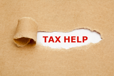 tax tips: The text Tax Help appearing behind torn brown paper.
