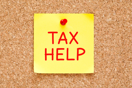 tax tips: Tax Help written on yellow sticky note pinned with red push pin on cork board.