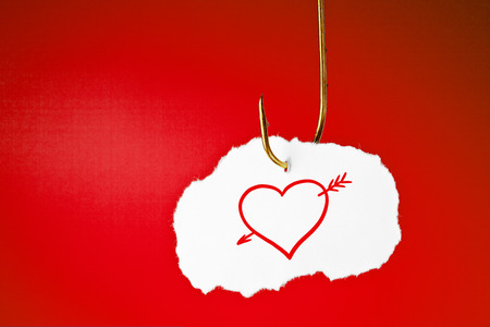 pierced: A heart pierced with an arrow drawn on white piece of paper hanging on a fishing hook over red background.