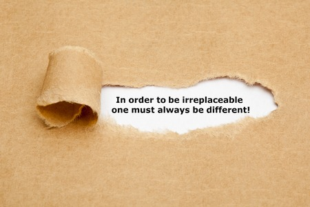 standout: The motivational quote In order to be irreplaceable one must always be different, appearing behind torn paper. Stock Photo