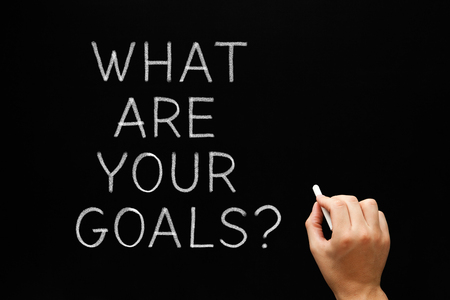 accomplishing: Hand writing What Are Your Goals with white chalk on blackboard.