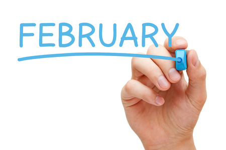 february: Hand writing February with blue marker on transparent wipe board.