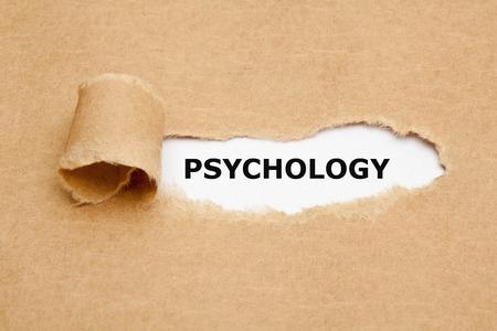 La parola psicologia che compare dietro strappata di carta marrone.