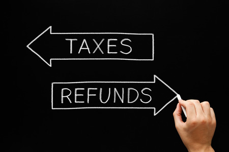 refunds: Hand sketching Taxes Refunds arrows concept with white chalk on blackboard.