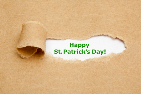 irish culture: The text Happy St.Patricks Day appearing behind torn brown paper.