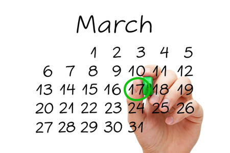 17 march: Hand putting mark on March 17 on calendar with green marker on transparent wipe board. Saint Patricks Day concept. Stock Photo
