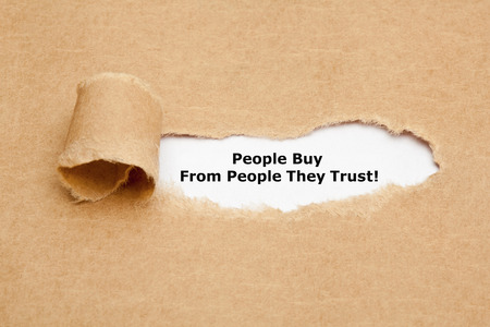trust people: The motivational quote People Buy From People They Trust, appearing behind torn brown paper.
