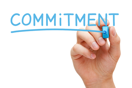 Hand writing Commitment with blue marker on transparent wipe board isolated on white.