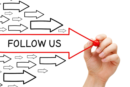 follow us: Hand drawing Follow Us arrows concept with marker on transparent wipe board. Stock Photo