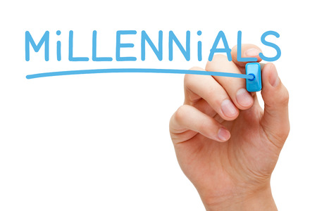 generational: Hand writing Millennials with blue marker on transparent wipe board.